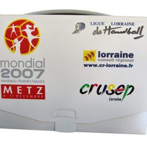 Valisette publicitaire réalisée à l'occasion du monde féminin de handball en 2007. Il y a plusieurs logos sur cette valisette publicitaire : le conseil régional de lorraine, le crusep et la ligue lorraine de Handball